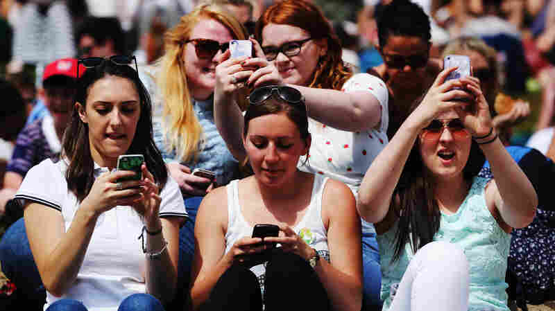 Tennis fans at this year's Wimbledon will have to take selfies the old-fashioned way, like these fans at last year's championships.