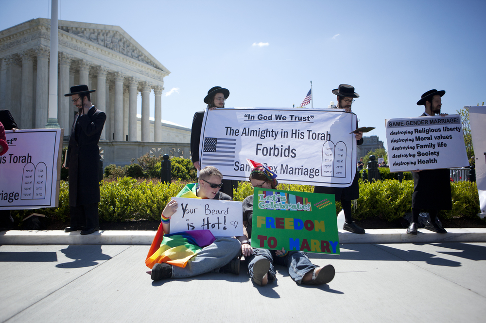 Michelle McKelvey (left) and Meg McKelvey sit near demonstrators outside of the Supreme Court on Tuesday. They have been together for two years.
