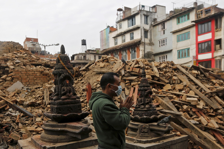 A man prays Tuesday morning next to rubble of a temple destroyed in Saturday's earthquake in Kathmandu, Nepal. (Adnan Abidi/Reuters/Landov)