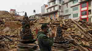 A man prays Tuesday morning next to rubble of a temple destroyed in Saturday's earthquake in Kathmandu, Nepal.