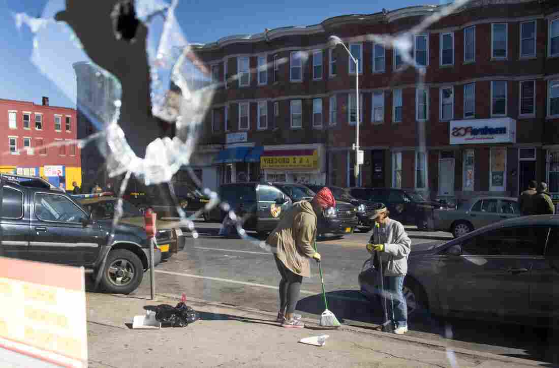 Two women sweeping up the streets are reflected in the broken window of a check cashing store in Baltimore, Maryland, on Tuesday.