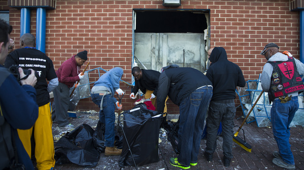 Maryland state troopers stand by Tuesday as people clean up outside a CVS pharmacy in Baltimore.