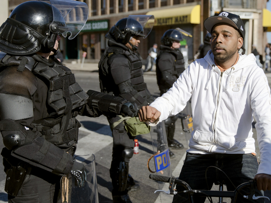 A man on a bicycle greets Maryland state troopers on Tuesday in the aftermath of rioting in Baltimore. (Matt Rourke/AP)