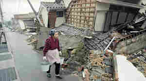 An elderly Japanese woman carries water past a home destroyed several days earlier on Jan. 17, 1995, by a powerful earthquake centered in Kobe, Japan. More than 6,000 people were killed and destruction was widespread, but the city was rapidly rebuilt.