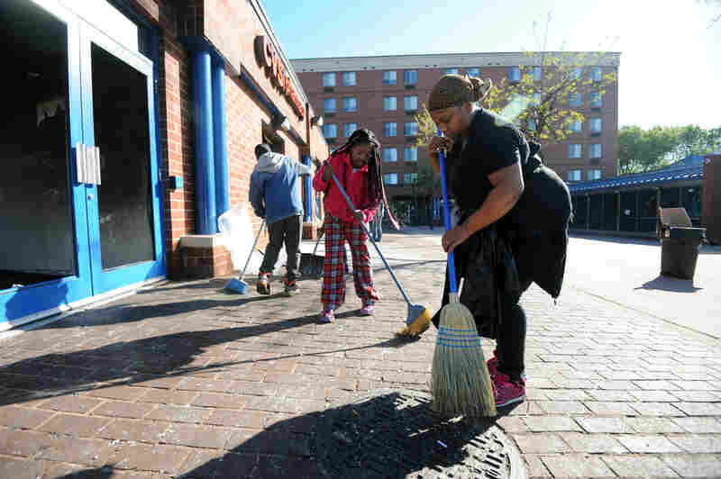 Ishawn Nelson (left), his sister Marae Nelson and LaQuicha Harper sweep the area outside a CVS that was looted and set on fire Monday.