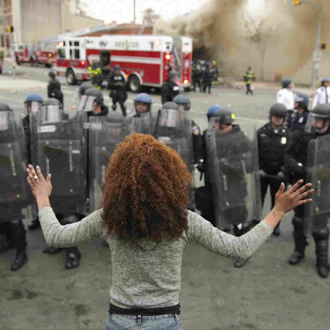 A woman faces a line of Baltimore police officers in riot gear.
