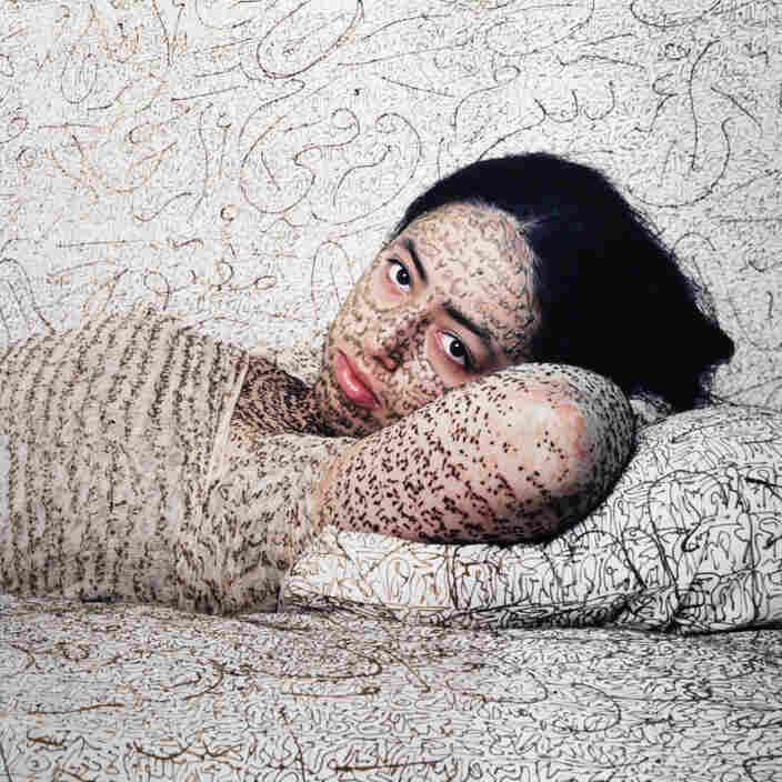 In her 2008 work Reclining Odalisque, Moroccan photographer Lalla Essaydi shows a woman covered in calligraphy.