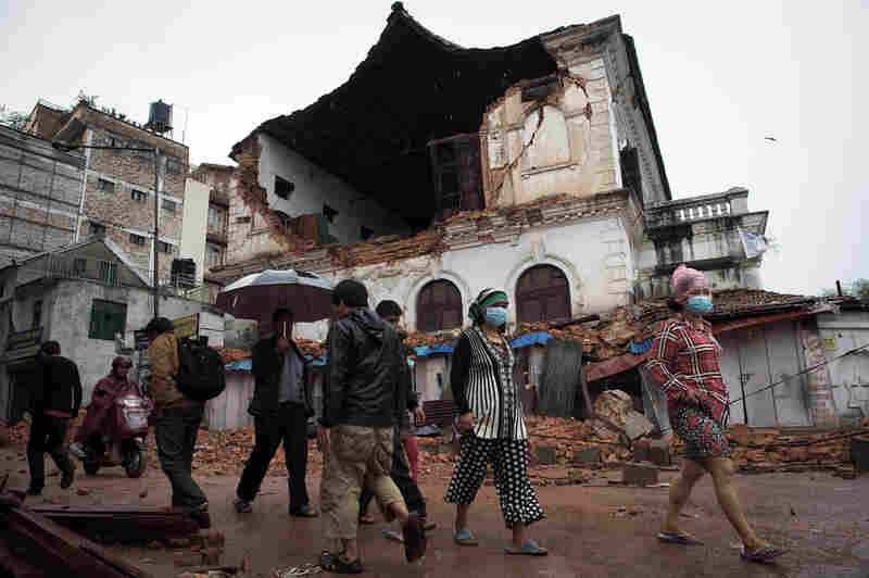 People walk in front of one of the oldest high schools in Kathmandu, which was damaged in the earthquake. Nearly 11,000 more were injured, according to Nepal's National Emergency Operation Center.