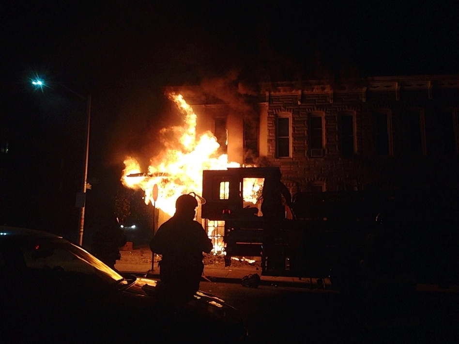 A police officer watches a corner market burn in the west side of Baltimore. (Eyder Peralta/NPR )