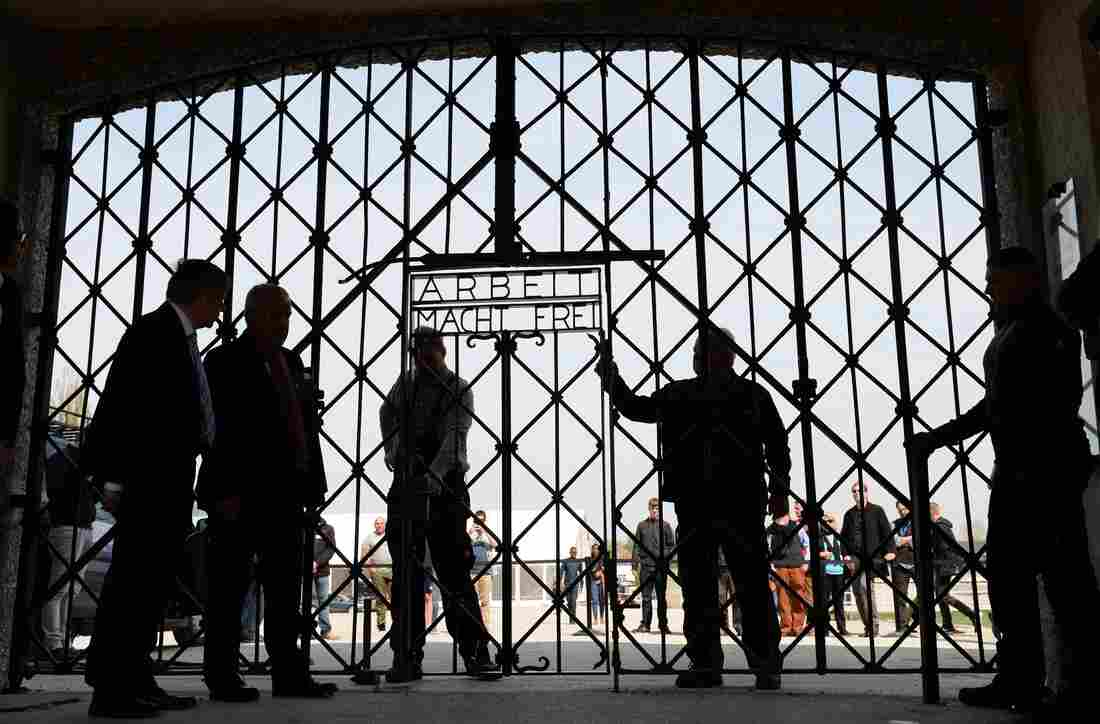 People stand beside the entrance gate of the former concentration camp in Dachau, southern Germany, on Wednesday. Dachau was opened in 1933, less than two months after Adolf Hitler became German chancellor, to house political prisoners. This week marks 70 years since U.S. forces liberated the camp.