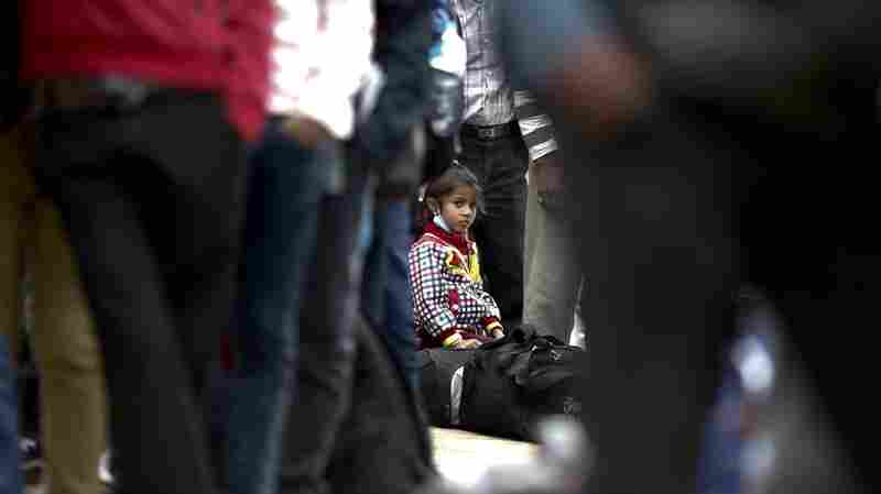 A young girl sits on her luggage as she waits in a long line with her family, hoping to board buses provided by the government to return to their homes outside Kathmandu.