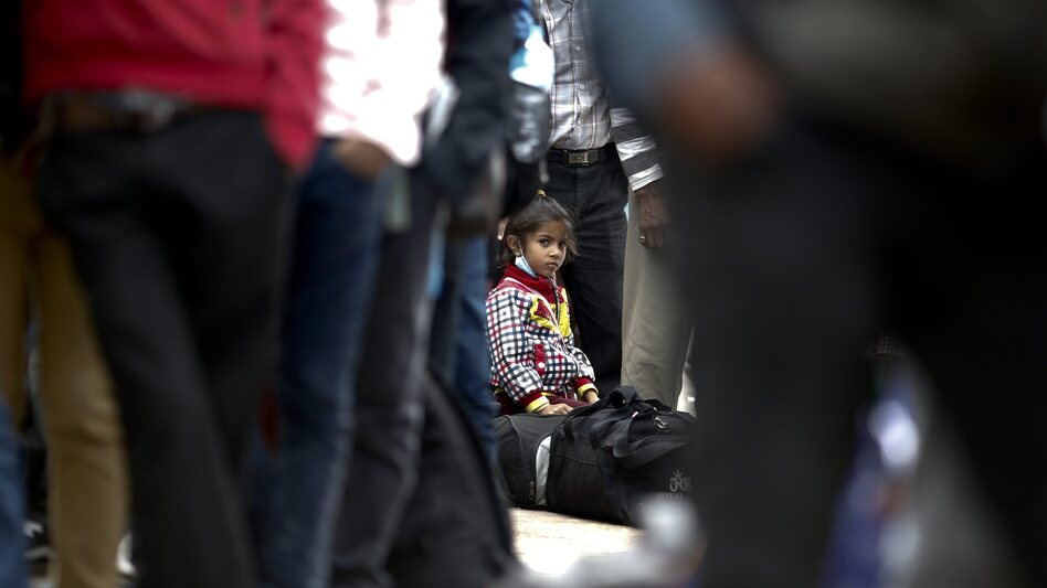 A young girl sits on her luggage as she waits in a long line with her family, hoping to board buses provided by the government to return to their homes outside Kathmandu. (Diego Azubel/EPA /LANDOV)