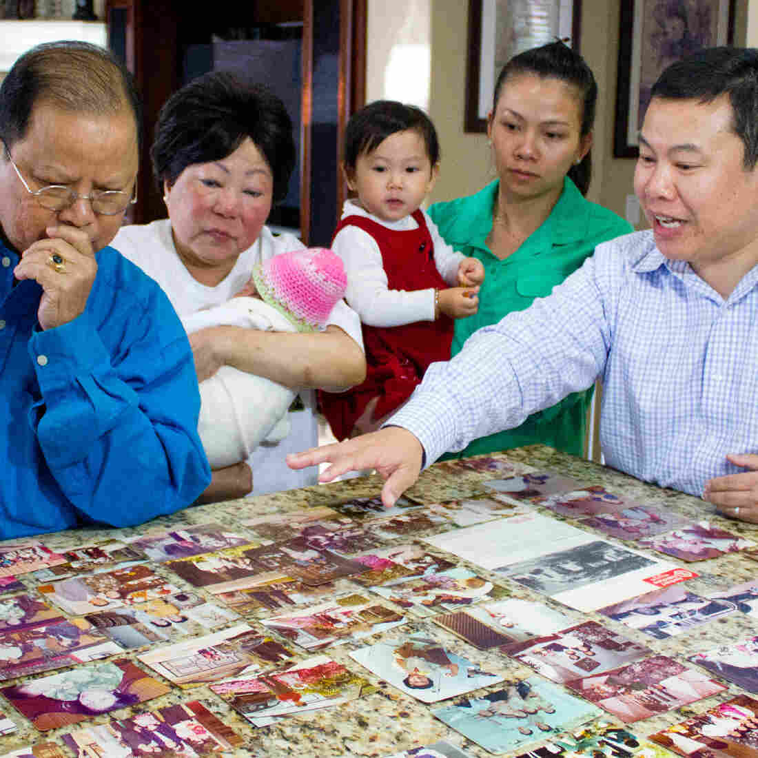Members of the Nguyen family, including Harry, Tammy, Elizabeth, Emma, Elly and Quan, look through family photos.
