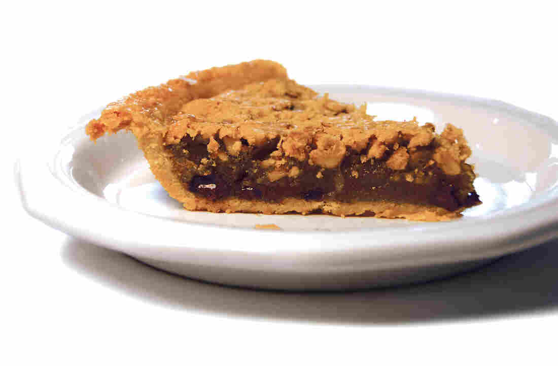 "A slice of ""Derby-Pie"" from Kern's Kitchen. The Kern family is said to have created the pie in 1950 as the signature item for a restaurant it used to operate. What people commonly call ""derby pie"" is like an embellished pecan pie: sticky, sweet filling made with bourbon and chocolate chips. Ironically, Kern's recipe is made without bourbon, and it uses walnuts instead of pecans."