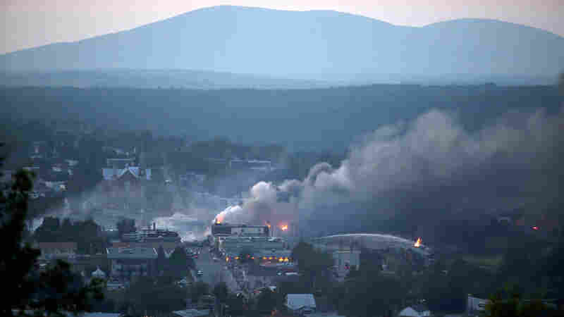 Firefighters douse blazes after a freight train loaded with oil derailed in Lac-Mégantic in Canada's Quebec province on July 6, 2013, sparking explosions that engulfed about 30 buildings in fire.