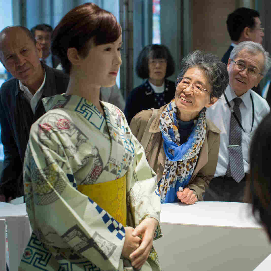 "Shoppers view and take photographs of humanoid robot ""Chihira"" at the information reception desk of Mitsukoshi department store in Tokyo."