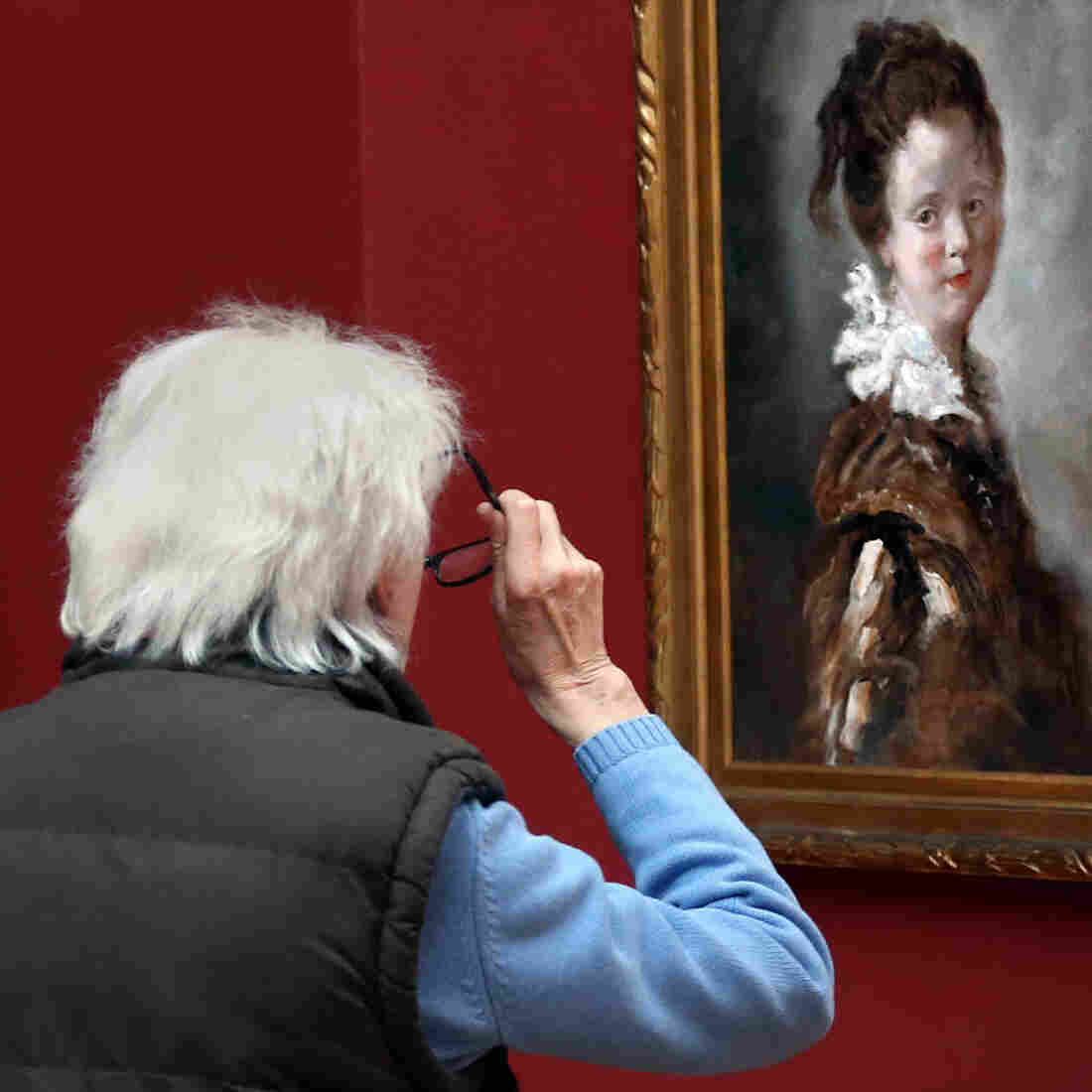 A visitor views a replica of Jean-Honore Fragonard's 18th century painting, Young Woman (right) as the original hangs to its left.