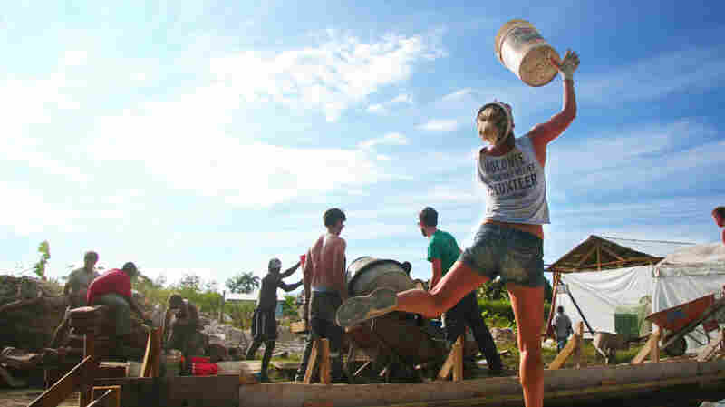 In Haiti after the earthquake, volunteers with All Hands toss buckets from the cement mixer back to the sand piles for a quick refill.