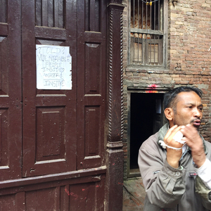 A man stands next to a homemade sign pleading for help in the ancient city of Bakhtapur, which was devastated by the earthquake.