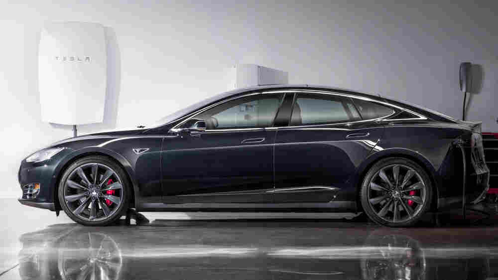 A photo released by Tesla shows its new Powerwall lithium-ion battery pack mounted on the wall (left) of a garage behind one of the company's electric cars.