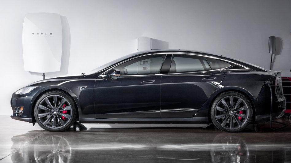A photo released by Tesla shows its new Powerwall lithium-ion battery pack mounted on the wall (left) of a garage behind one of the company's electric cars. (Tesla Energy)