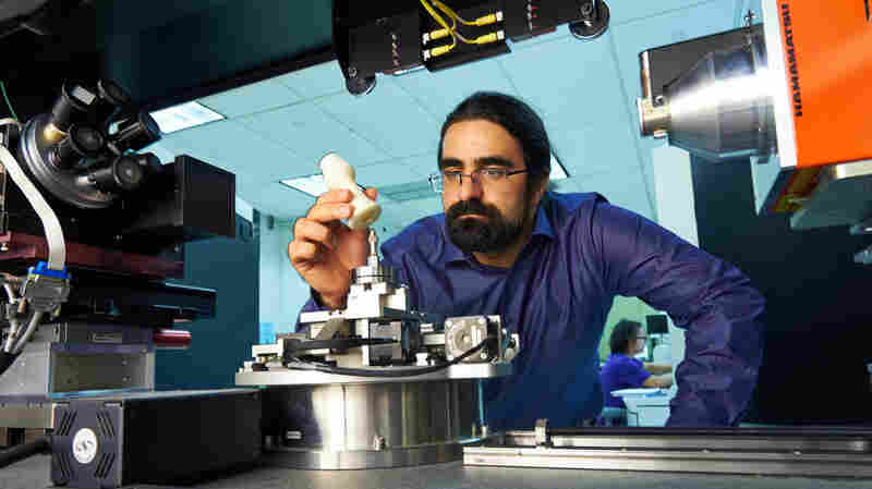 Sina Shahbazmohamadi places a 3-D printed copy of a recorder foot joint into a measuring device in a lab at the University of Connecticut's Center for Clean Energy Engineering.