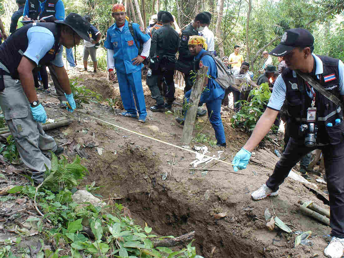 Thai policemen measure shallow graves in Songkhla province in southern Thailand on Saturday. Authorities say the 30 or so gravesites appear to contain remains of illegal migrants from neighboring Myanmar.