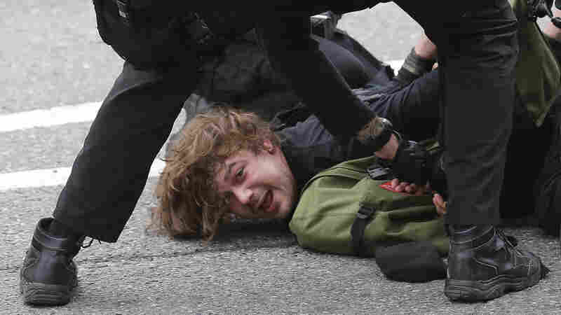 Police officers arrest a man during a May Day march, on Friday, in Seattle.