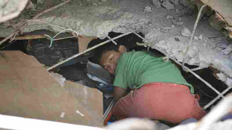 A boy crawls into the ruins of a collapsed building to look for usable things in Nepal's capital, Kathmandu, on Sunday. Officials say they have found three survivors in the rubble a full week after a powerful earthquake.
