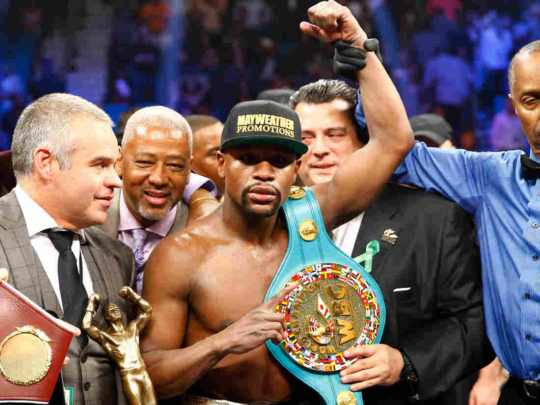 Floyd Mayweather Jr. celebrates the unanimous decision victory during the welterweight unification championship bout on Saturday at MGM Grand Garden Arena in Las Vegas.