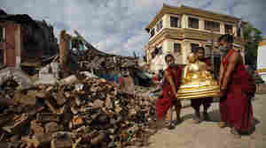 Buddhist monks recover a statue of a Buddhist deity from a monastery at Swayambhunath.
