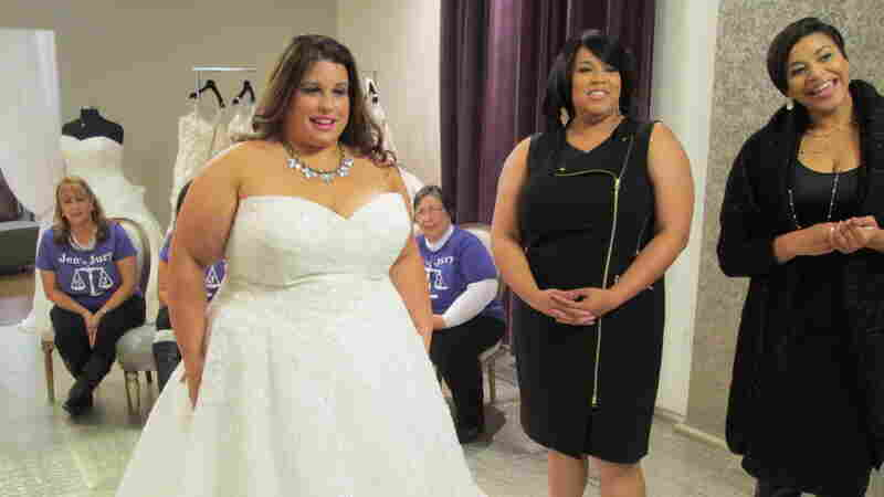Bride Jennifer Uniglicht tries on a gown at Curvaceous Couture, a bridal boutique specializing in plus-size designer gowns. Proprietors Yukia Walker and Yuneisia Harris (right) star in the new TLC show, Curvy Brides.