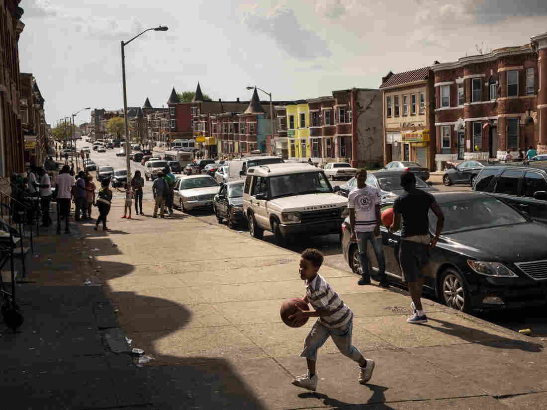 """A boy plays in the Sandtown neighborhood, where Freddie Gray was arrested, on April 30. """"Every day, this is the atmosphere,"""" Addison says. """"It's not an atmosphere of aggression. It's not an atmosphere of violence!"""""""