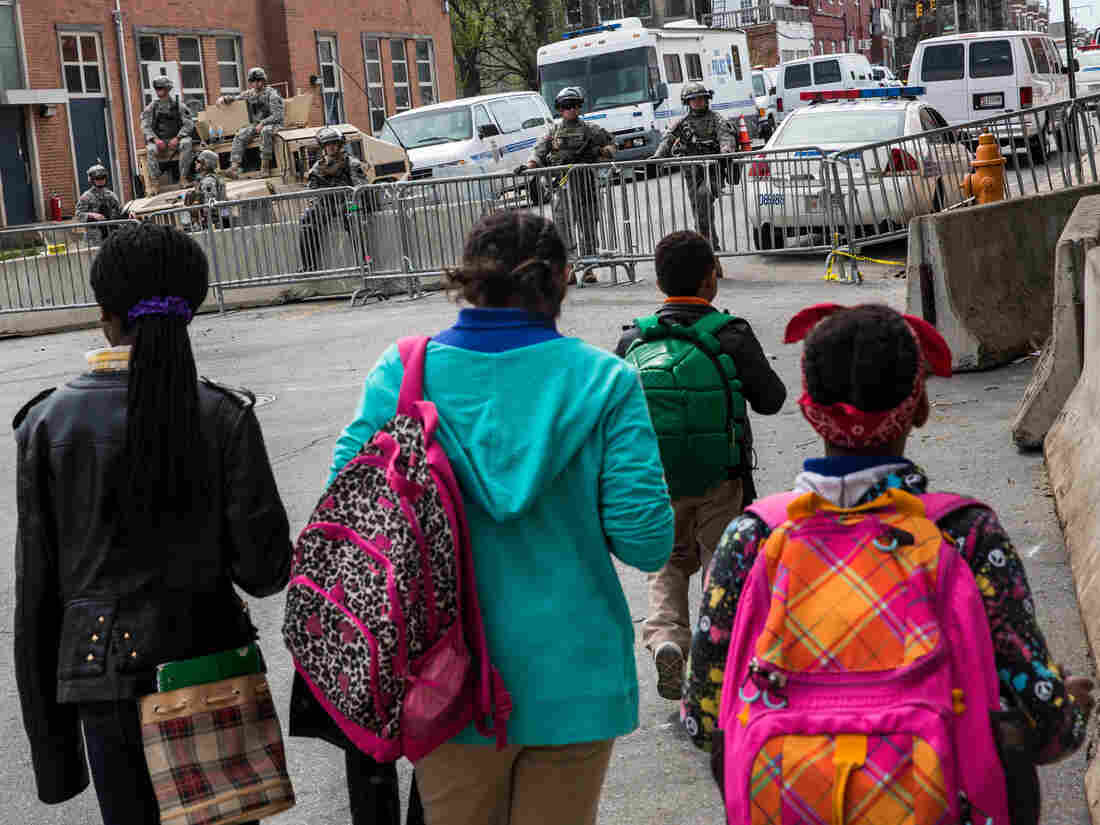 """Girls walk past a police station heavily guarded by the National Guard in the Sandtown neighborhood. """"Why do y'all have fully loaded M-16s next to kids?"""" Addison asks."""