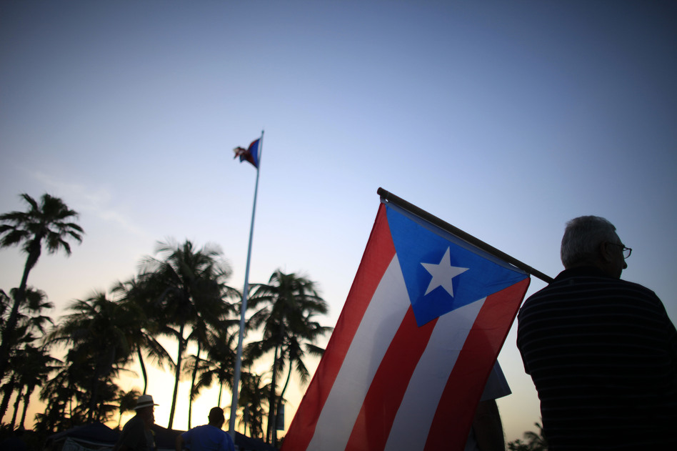 Protesters gather April 30 outside Puerto Rico's Capitol building in San Juan to oppose Gov. Alejandro Garcia Padilla's budget proposal. The plan would raise taxes to help cover the state's massive debt. (Ricardo Arduengo/AP)