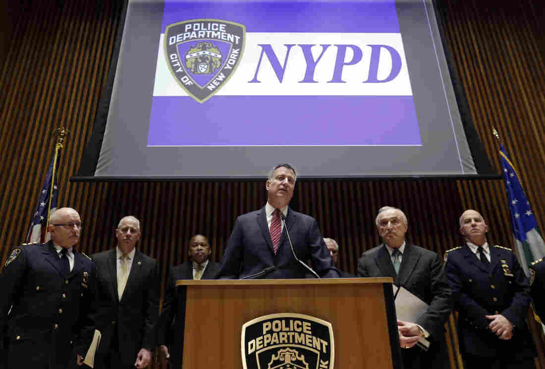 New York Mayor Bill de Blasio (center), City Police Commissioner William Bratton (second from right) and other NYPD officers address a news conference on Jan. 5. There is debate surrounding the citywide increase of low-level crime enforcement, otherwise known as the broken windows approach to policing.