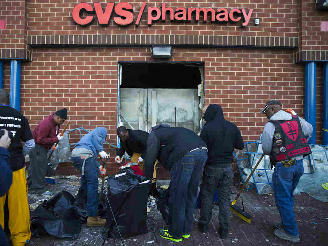 Baltimore residents clean up outside a CVS store Tuesday, after an evening of riots following the funeral of Freddie Gray.