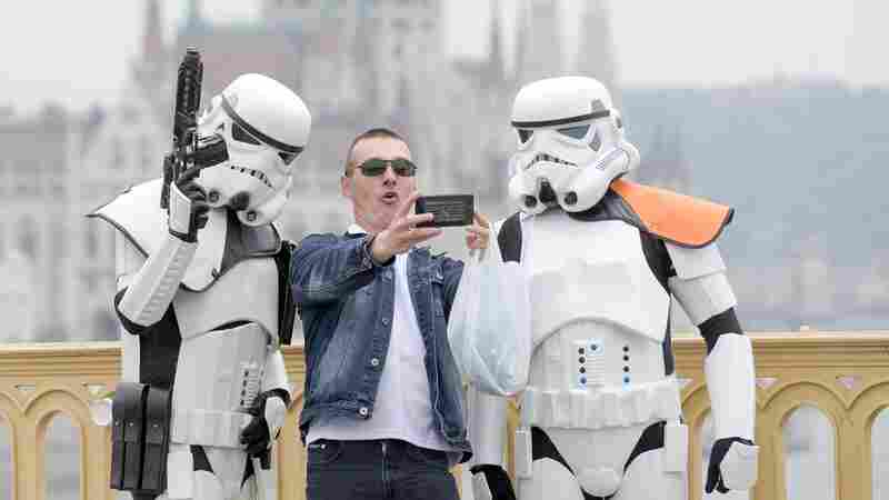 In Budapest, Hungary, a man takes a photo with people dressed as their favorite Star Wars stormtroopers.