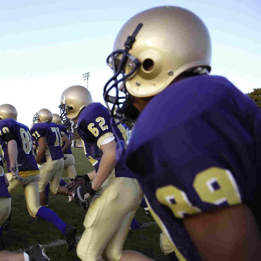 A high school football team charges onto the field.