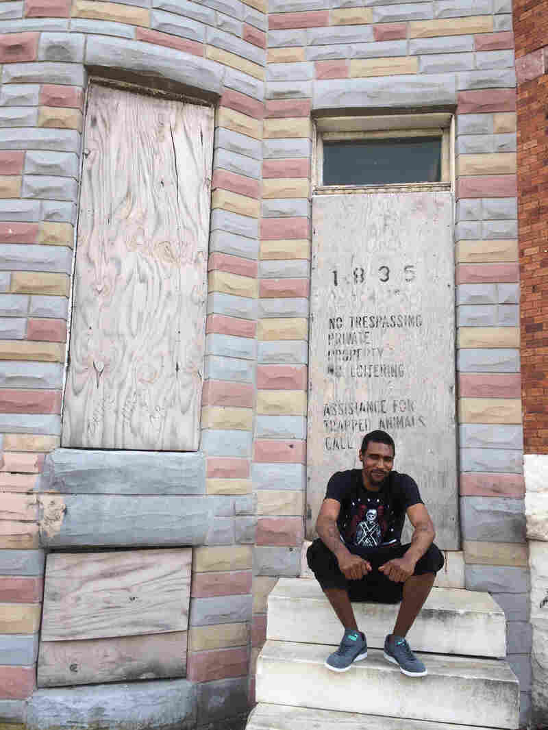 Travon Addison sits at the house he grew up in, bought by his great-grandmother, he thinks, in 1920. His family members had to abandon the home 15 years ago because they couldn't afford to fix it.