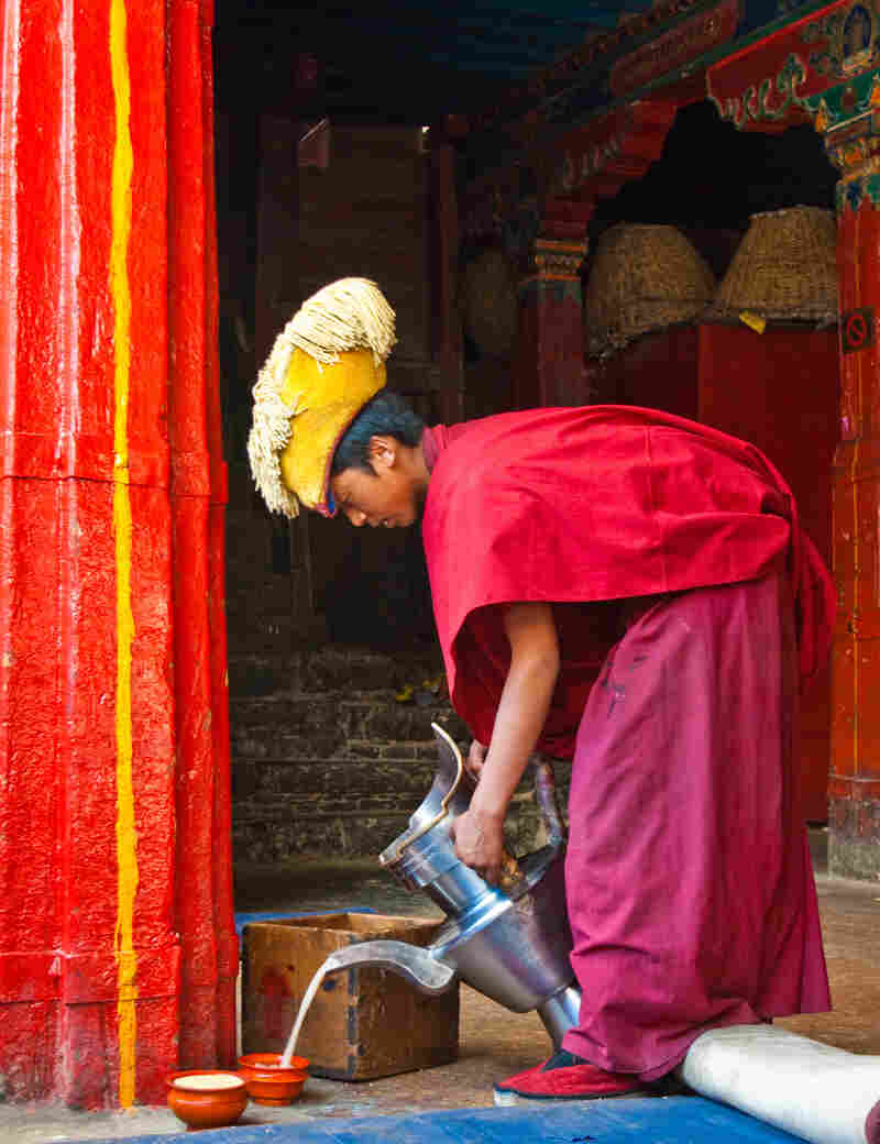 A monk pours butter tea at the Tashilhunpo Monastery in Tibet.