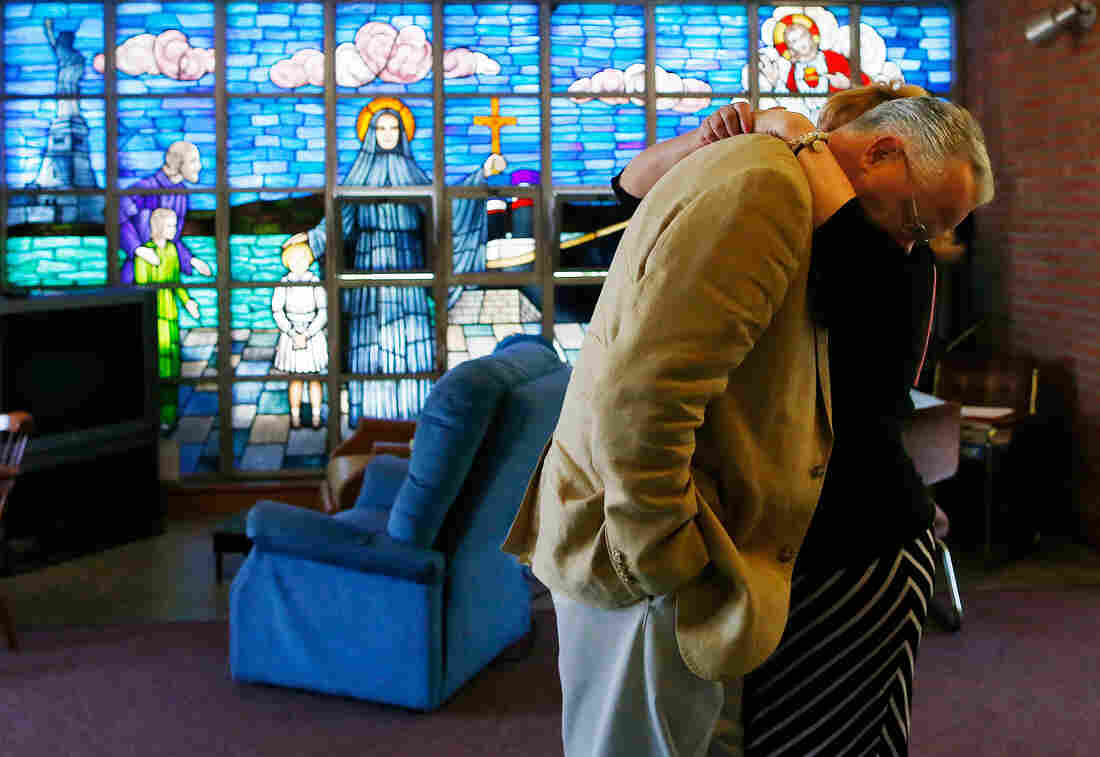 Jon Rogers is hugged by his wife, Maryellen, following services at St. Frances Xavier Cabrini Church in Scituate, Mass., in June 2014.