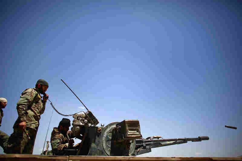Afghan soldiers shoot at suspected Taliban members in Tazir Abad and the parched hills beyond.