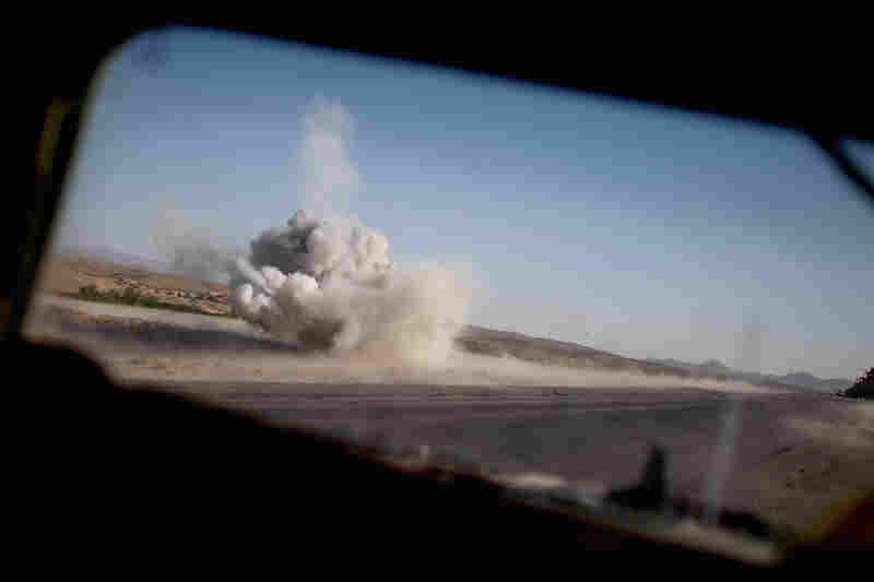 An Afghan mine-clearing team safely detonates a roadside bomb planted near Highway One.