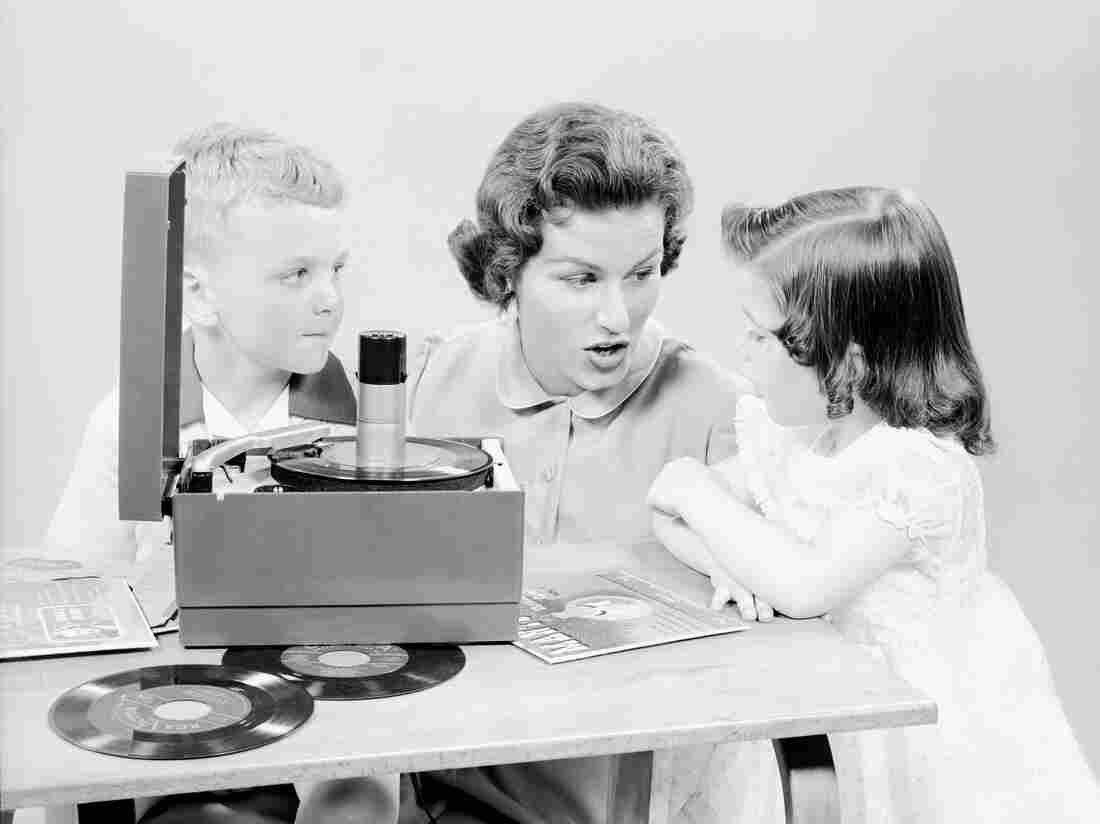 A mother explains the vast intricacies of a portable turntable to her children in the 1950s.
