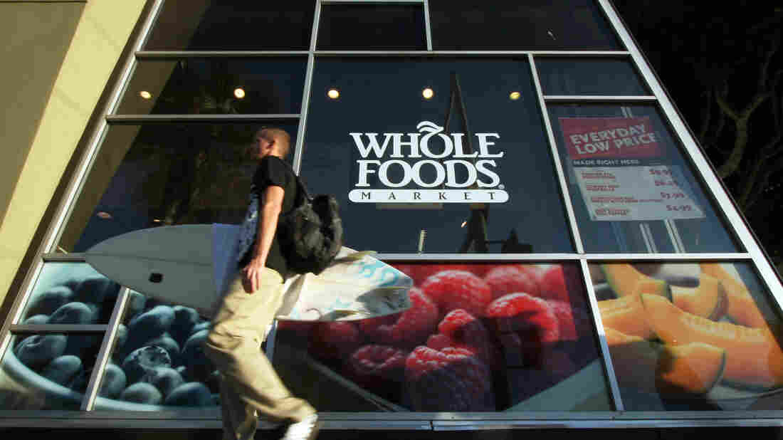 A man carries a surfboard past a Whole Foods store in Santa Monica, Calif. Whole Foods Market Inc. reported underwhelming second-quarter earnings on Wednesday.