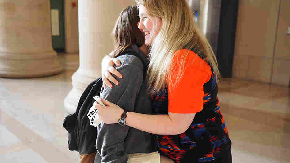 TMAYD founder Izzy Lloyd (right) gives a friend a hug after asking about her day.