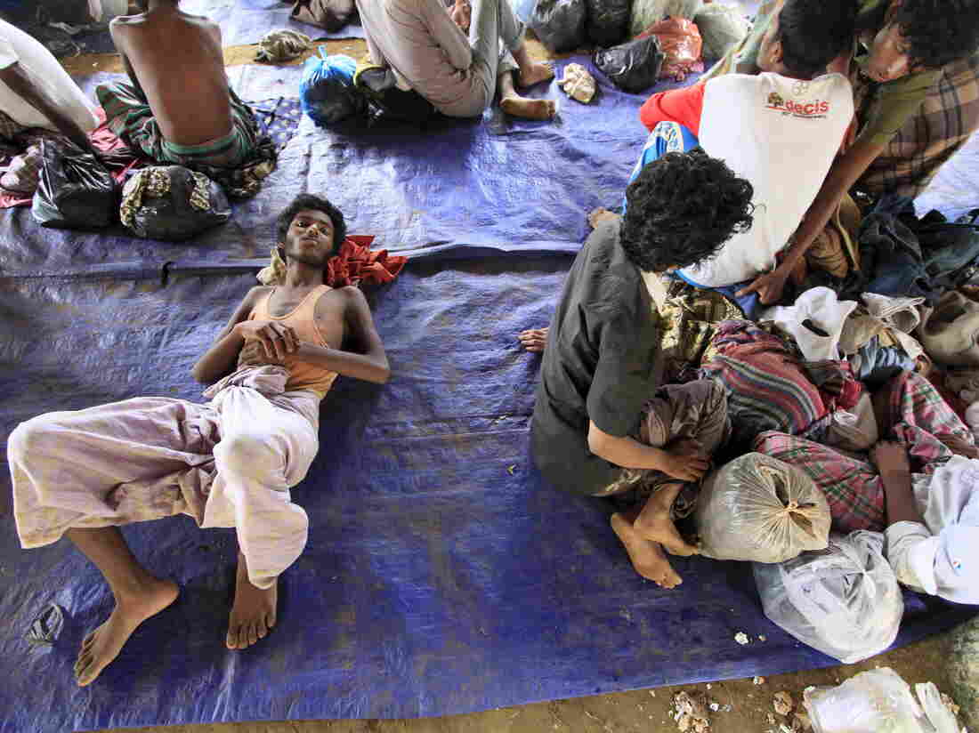 Rohingya refugees sit on a plastic sheet at Matang Raya village, Baktya district in Aceh Utara, Aceh province, Indonesia, on Sunday. Nearly 600 migrants thought to be Rohingya refugees from Myanmar were rescued from two wooden boats stranded off the coast of Indonesia's northern Aceh province, authorities said.