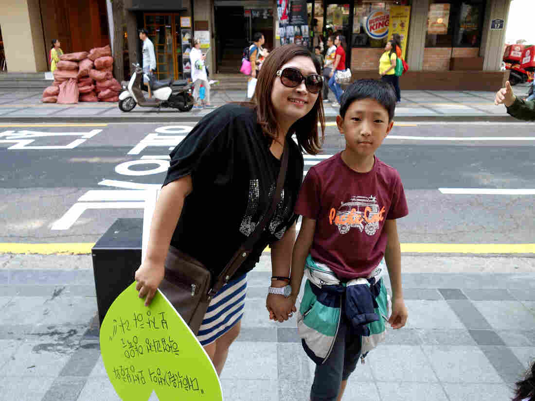 Choi Hyong-sook and her 11-year-old son during a march on Single Mother's Day. Her decision to raise him alone cost her ties with her family and a string of jobs.