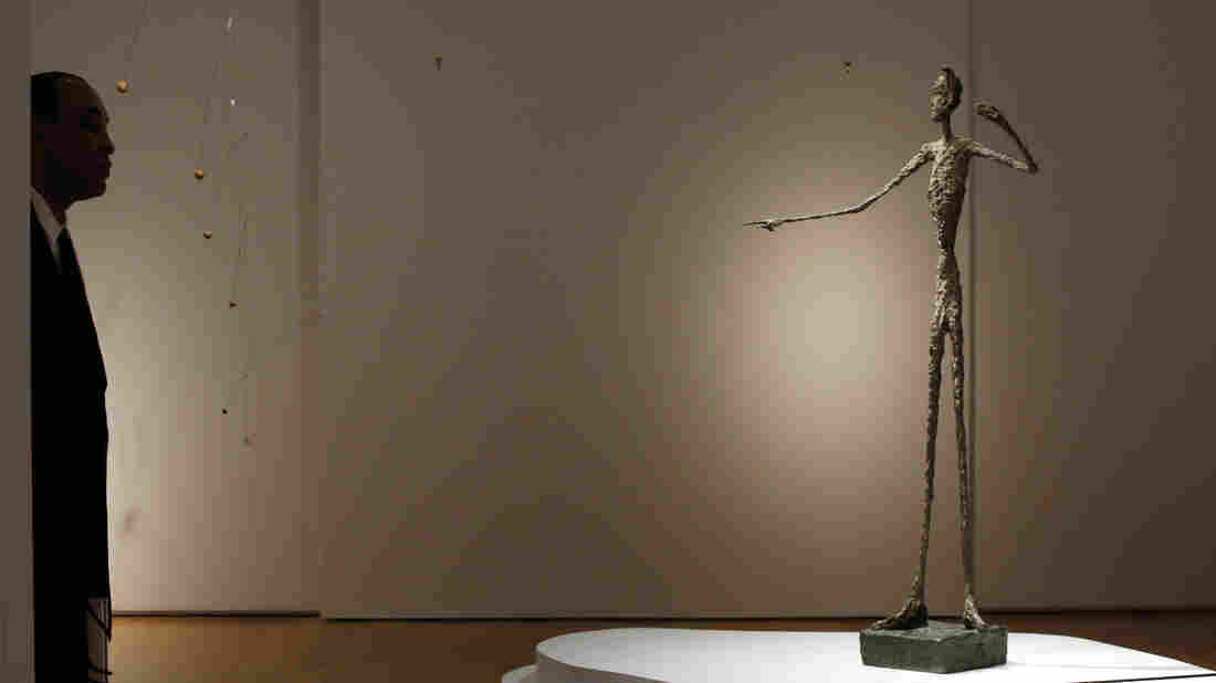 A guard stands beside Alberto Giacometti's life-size bronze sculpture Pointing Man after it sold for more than $141 million Monday, earning it the title of most expensive sculpture sold at auction — a title it took from another Giacometti sculpture sold for more than $100 million in 2010.